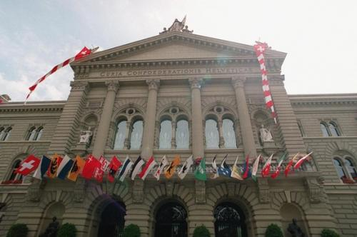Swiss parliament building decorated with flags of the cantons